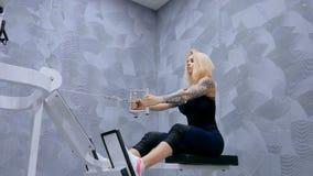 Athletische junge Frau, die auf Eignungsübungsausrüstung ausarbeitet Stockfoto