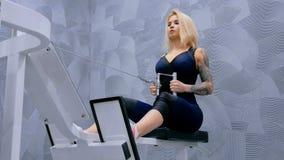 Athletische junge Frau, die auf Eignungsübungsausrüstung ausarbeitet Stockfotos