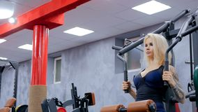 Athletische junge Frau, die auf Eignungsübungsausrüstung ausarbeitet Stockbild