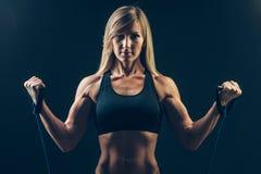 Athletische junge Frau, die an Bizeps mit arbeitet stockfotos