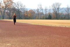 Athletische junge Frau, die an der Spur ausdehnt Stockfoto