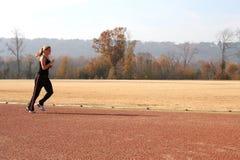 Athletische junge Frau, die an der Spur ausdehnt Stockbild