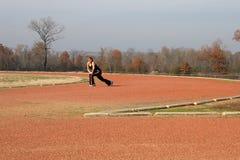 Athletische junge Frau, die an der Spur ausdehnt Stockfotos