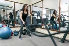Athletische junge Frau, die in der Turnhalle unter Verwendung der Kampfseile trainiert Eignung, Sport, Training, Leute, gesundes  stockfotografie