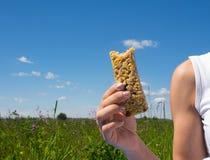 Athletische junge Frau, die draußen Getreideschokoriegel isst Gesundes Lebensstilkonzept Stockfotografie