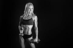 Athletische junge Frau, die ein Eignungstraining mit dumbbels tut Stockfotos