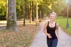 Athletische junge Frau, die in einem Park rüttelt Lizenzfreies Stockfoto