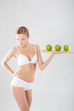 Athletische junge Frau, die einen grünen Apfel hält Lizenzfreie Stockfotografie