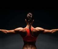 Athletische junge Frau, die Muskeln der Rückseite zeigt Stockfotografie