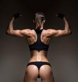 Athletische junge Frau, die Muskeln der Rückseite zeigt Lizenzfreie Stockfotos