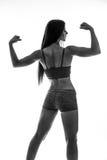 Athletische junge Frau, die Muskeln von Händen zeigt Stockbild