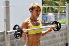 Athletische junge Frau, die Training mit dem Barbell im Freien tut Stockbilder