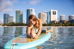 Athletische junge Frau in SUP Yogapraxisfront-Biegung Haltung im Ala Stockfotos