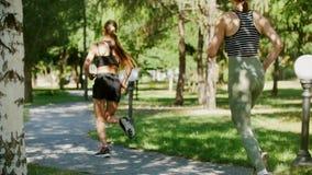 Athletische Mädchen, die in den Park auf der Bahn und mit ihnen ein Hunderasseschlittenhund laufen stock footage