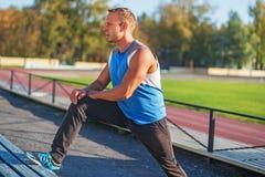 Athletische Mannzüge, ausgedehnt auf Bankstadion Stockfotos