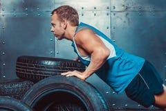 Athletische Mannzüge, gedrückt von einem Autoreifen Lizenzfreies Stockbild