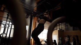 Athletische muskulöse Frau, die auf der horizontalen Stange in der Zeitlupe schwingt stock video