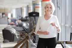 Athletische reizend ältere Frau, die Rest während des Turnhallentrainings hat stockfotografie