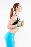 Athletische rothaarige Frau in der hellen Sportkleidung tut Übung mit kleinen grünen Dummköpfen Lizenzfreies Stockfoto