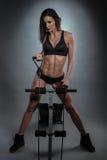 Athletische sexy junge Frau, die an der Rudermaschine aufwirft Stockbilder