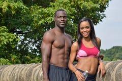 Athletische und geeignete Afroamerikanerpaare - pausierend während, arbeiten Sie aus lizenzfreies stockbild