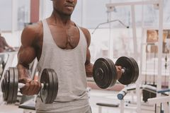Athletischer afrikanischer Mann, der mit Dummk?pfen an der Turnhalle ausarbeitet lizenzfreie stockfotos