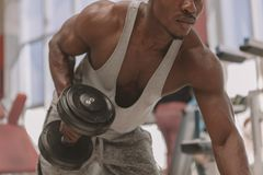 Athletischer afrikanischer Mann, der mit Dummk?pfen an der Turnhalle ausarbeitet stockbilder