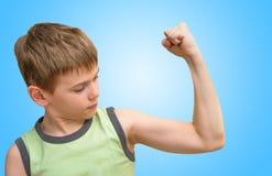 Athletischer Junge, der den Bizepsmuskel betrachtet Stockbilder