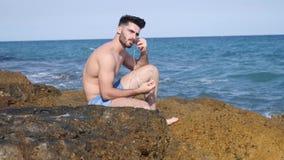 Athletischer junger Mann auf Strand hörend Musik stock video