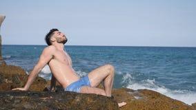 Athletischer junger Mann auf Strand hörend Musik stock video footage