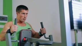 Athletischer junger Mann, der Übungsmaschine an der Turnhalle verwendet stock video