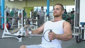 Athletischer junger Mann, der auf einem blockorientierten Gerät trainiert Porträt des starken athletischen Mannes am Turnhallentr