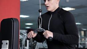 Athletischer junger Mann, der ?bungen f?r die Muskeln der Arme und der Schultern auf Simulatormaschine tut stock video
