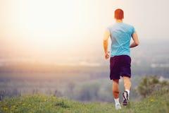 Athletischer junger Mann, der in die Natur läuft Stockbild