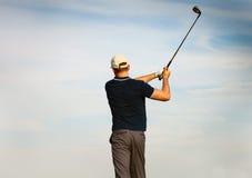 Athletischer junger Mann, der Golf, Golfspieler schlägt Fahrrinnenschuß spielt Lizenzfreies Stockfoto
