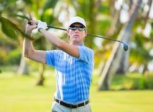 Athletischer junger Mann, der Golf spielt Stockfoto