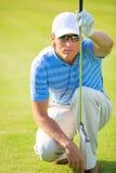 Athletischer junger Mann, der Golf spielt Stockbild