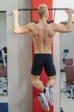 Athletischer junger Mann, der von der Turnhallenausrüstung hängt Stockbild