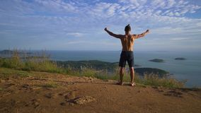 Athletischer junger Mann hebt seine Hände an, die oben am Rand des Berges stehen stock footage