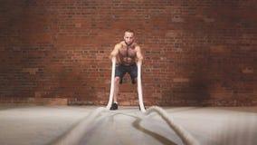 Athletischer junger Mann mit dem Kampfseil, das Übung in der Funktionsausbildungseignungsturnhalle tut Langsame Bewegung stock video footage