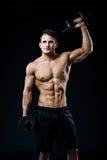 Athletischer Kerl der perfekten Passform, der mit Barbellplatte in der Turnhalle, im perfekten Latmuskel, in den Schultern, im Bi Stockfoto