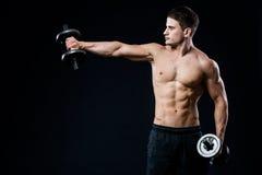 Athletischer Kerl der perfekten Passform, der mit Barbellplatte in der Turnhalle, im perfekten Latmuskel, in den Schultern, im Bi Lizenzfreie Stockfotografie