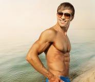 Athletischer Kerl in der Sonnenbrille auf dem Strand Lizenzfreie Stockfotografie