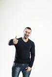 Athletischer Kerlbodybuilder in den Jeans und in T-Shirt, die Geste zeigen Lizenzfreie Stockbilder