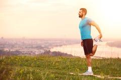 Athletischer Läufer, der Übung ausdehnend tut Stockfotos