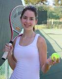 Athletischer Mädchenholdingtennisschläger und -kugel lizenzfreie stockbilder