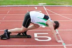 Athletischer Mann auf der Anfangszeile für ein Rennen Lizenzfreies Stockfoto