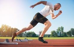 Athletischer Mann auf der Bahn, die beginnt zu laufen Gesundes Eignungskonzept mit aktivem Lebensstil Lizenzfreie Stockfotos