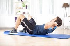Athletischer Mann, den das Handeln sich kräuselt, Ups Übung zu Hause Stockfotos