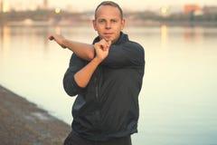 Athletischer Mann, der Übung auf dem Strand bei Sonnenuntergang tut Lizenzfreies Stockbild